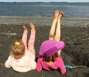 girls at beach legs in air